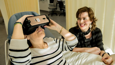Prince of Wales Hospital is trialing VR therapy to help patients recover. Pictured is Theodora Michalopoulos wearing a VR headset as former patient Stefanie Ammann looks on.